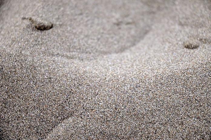 Мелкий темный песок