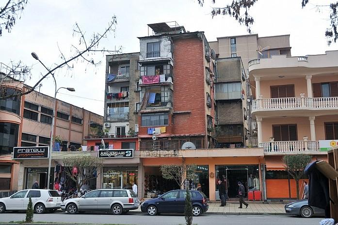 Жилые кварталы выглядят так: непонятной формы дом, балконы, увешанные бельем и серые деревья вокруг
