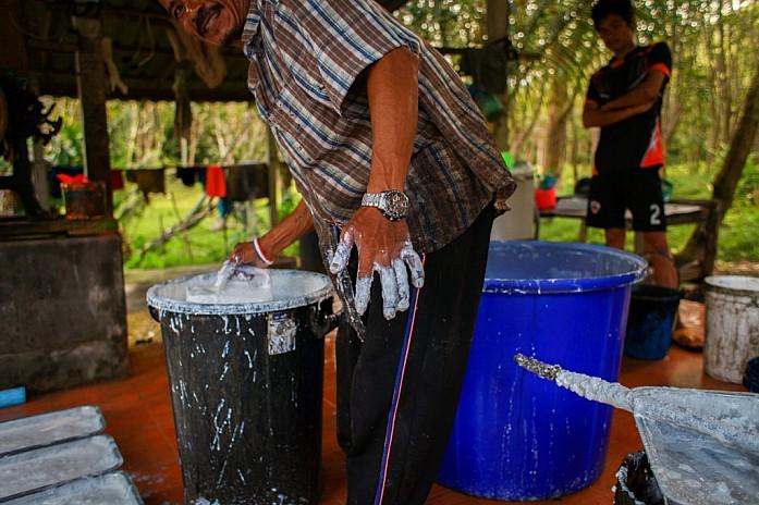 Фермер разливает каучуковую смесь по формам